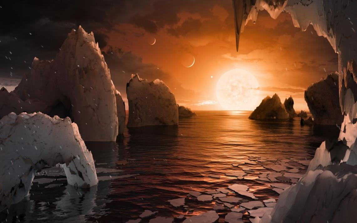 """An artist's impression of the perpetual sunrise that might greet visitors on the surface of planet TRAPPIST-1f. If the planet is tidally locked, the """"terminator region"""" dividing the night side and day side of the planet could be a place where life might t"""
