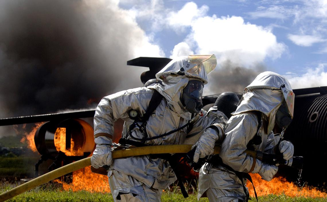 Air Force firefighters work to put out a fire as part of a simulated aircraft crash during an exercise at Andersen Air Force Base in Guam. The routine exercise is conducted at the base a few times a year to sharpen the mobility and wartime capabilities of