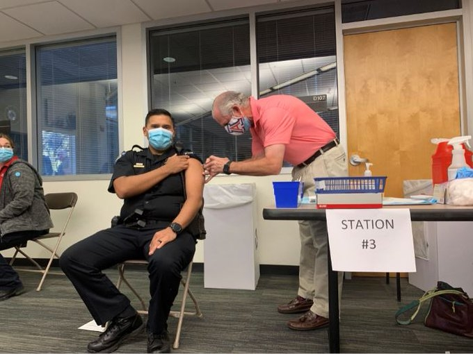 President Robert C. Robbins vaccinates a police officer