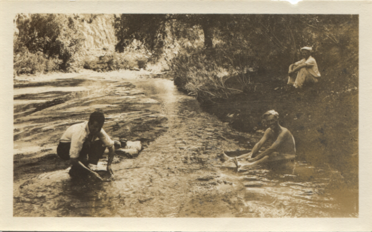 Men sit near the Santa Cruz River