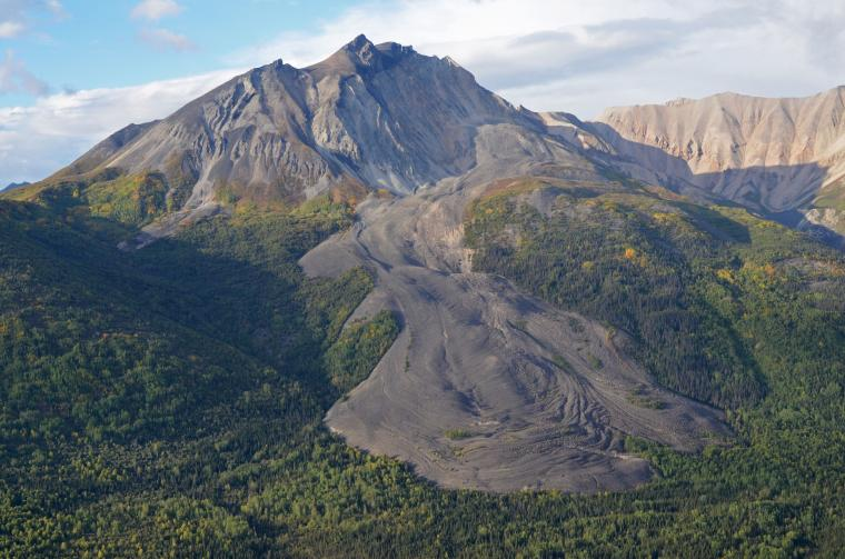 Deceptively similar to a lava flow, the grey mass flowing at the base of Sourdough Peak near McCarthy, Alaska, is actually a glacier blanketed by rocky debris. Jack Holt and his team at the Lunar and Planetary Laboratory have spent years hiking and skiing