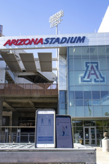 two smartphones with Covid Watch app installed outside Arizona Stadium