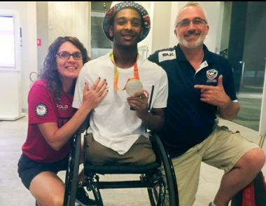 Josh wearing his silver Paralympic medal with his mom and dad, Laura and Matthew Brewer.