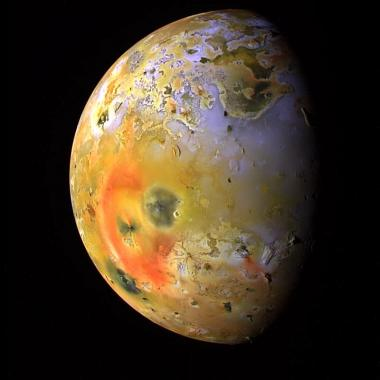 Io illuminated by the sun, with Pele's red deposits featured prominently.