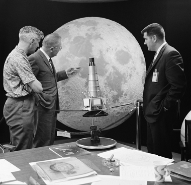 Gerard Kuiper points out features on a lunar hemisphere to team members Ewen Whitaker  and Ray Heacock. On the table is a model of the Ranger  spacecraft, which took the first close-up images of the moon. The lunar hemisphere is on display at UA's Flandra