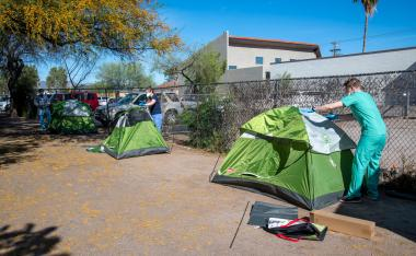 From left: University of Arizona medical students Christian Bergman, Erika Krall and Christopher Vance set up camping tents on the property of Z Mansion to serve as isolation units for homeless people suspected to have COVID-19.